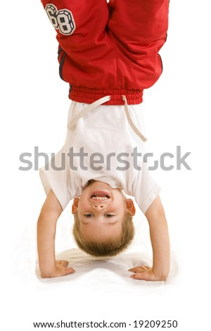 An adorable three year old doing a handstand. - stock photo
