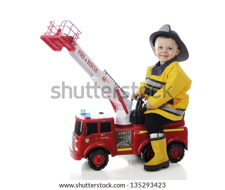 An adorable toddler happily playing fireman on his toy fire truck.  On a white background. - stock photo