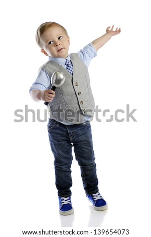 An adorable 2-year-old boy giving his grand finale with a microphone in one hand and his other extended.  On a white background. - stock photo