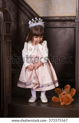 An adorable 2-year-old girl and her toy bear. Little Princess look at his toy. Portrait in the interior - stock photo