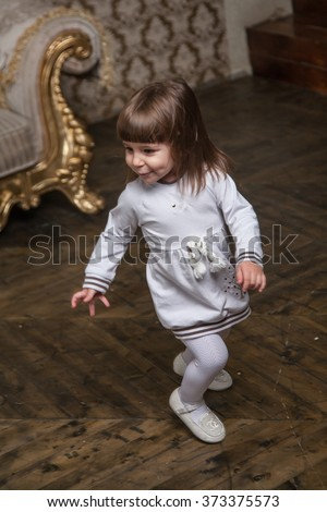 An adorable 2-year-old girl has fun and runs around the room - stock photo