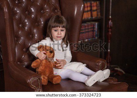 An adorable 2-year-old girl is sad. Little Princess and her toy bear sitting in a chair . Portrait in full growth in the interior  - stock photo
