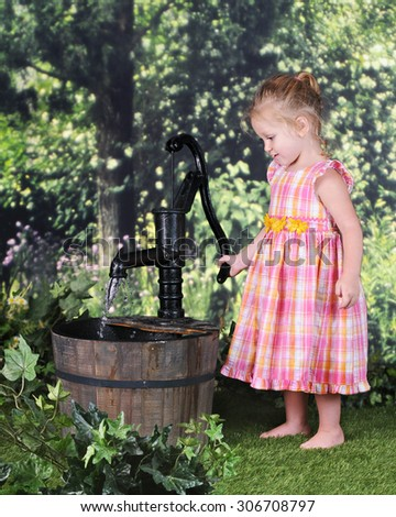 An adorable 2 year old happily pumping water with an old pump on a warm summer day. - stock photo