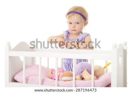 An adorable 2-year-old holding a baby bottle in her hands while standing by her doll crib containing two dolls.  On a white background. - stock photo