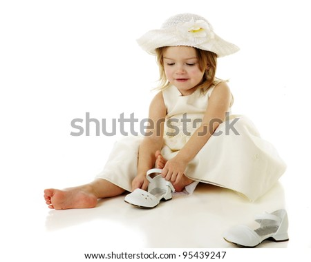 An adorable 2 year-old in dressy white clothes putting on her own shoes.  On a white background. - stock photo