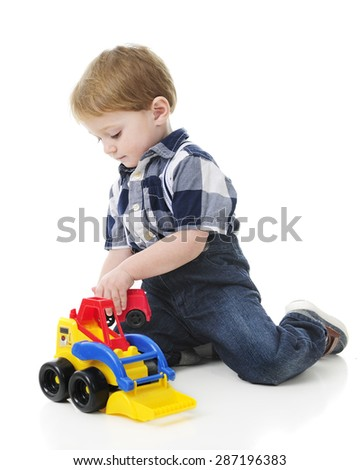 An adorable 2-year-old playing on the floor with a toy front loader.  On a white background. - stock photo