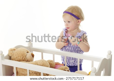 An adorable 2-year-old standing by her doll crib ready to feed her toy bear from a baby bottle.  On a white background. - stock photo
