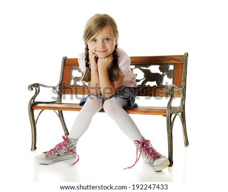 An adorable young elementary girl sitting on a park bench with sparkly, oversized, high-top sneakers tied with neon pink laces covered with hearts.  On a white background. - stock photo