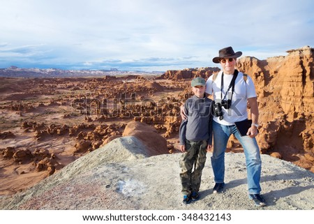 An adult and a child standing in front of Goblin Valley State Park, Utah, US - stock photo