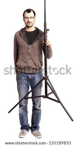 An adult caucasian man on his 30's looking at the camera with a serious and somewhat worried gaze, caught in the middle of contemplating the lighting setup he's creating. Isolated on white background. - stock photo