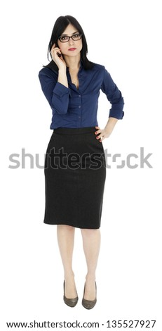 An adult (early 30's) black haired caucasian woman, wearing a blue buttoned shirt and a dark gray skirt; looking at the camera while listening on the phone. Isolated on white background. - stock photo