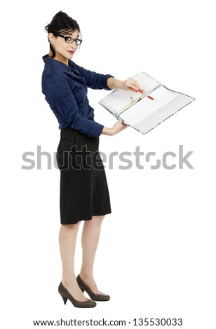 An adult (early 30's) woman holding a ring binder folder and pointing with her pen to a certain detail in the document while giving an eager expression to the camera. Isolated on white background. - stock photo