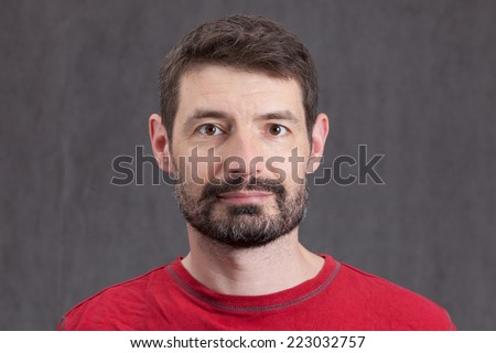 An adult male in his early forties with a full beard wearing a red tshirt.  He is smiling and looking directly at the camera. - stock photo