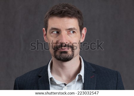 An adult male in his early forties with a goatee beard wearing a jacket and shirt.  He is smiling and looking to the right. - stock photo