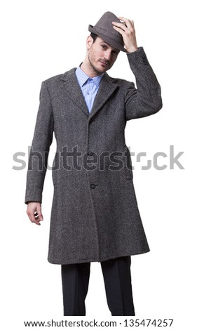 An adult male wearing an overcoat and raising his hat a little above his head, in a greeting gesture. Isolated on white background. - stock photo