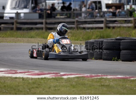 An adult racing go-kart coming out of a bend. - stock photo