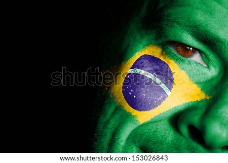 An adult sports fan with his face painted in the colors of Brazil's flag - stock photo