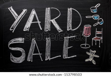 An advertisement or announcement of a Yard Sale on a used blackboard. Yard sales are a traditional way to make money and clear out unwanted or old belongings from your home. - stock photo