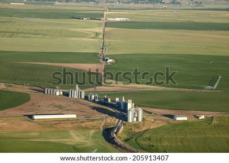 An aerial view of farm granaries for storing cereal grains with railroad access, and farm fields in the background - stock photo
