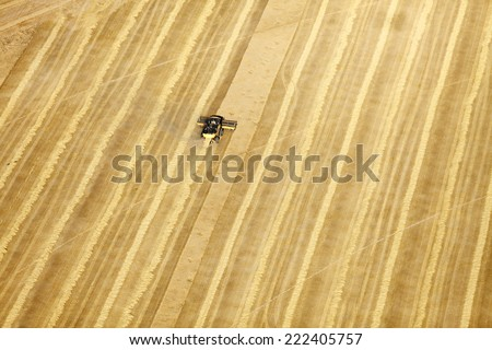 An aerial view of farm machinery in the field harvesting wheat - stock photo