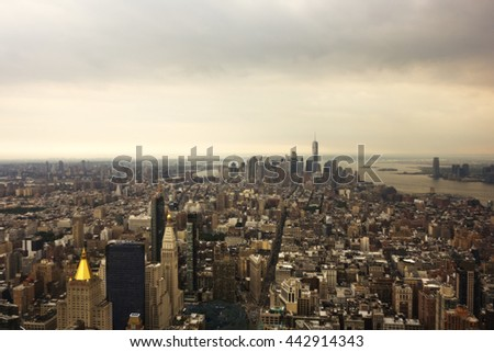 An aerial view of New York City buildings and skyscrapers.  The Freedom Tower and Statue of Liberty can be seen in the distance. - stock photo