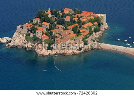 An aerial view of Sveti Stefan the resort on its peninsula with the causeway connecting to the surrounding beaches and the blue water of the Adriatic Sea. - stock photo