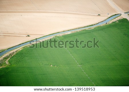An aerial view of two tractors planting potatoes in a field - stock photo