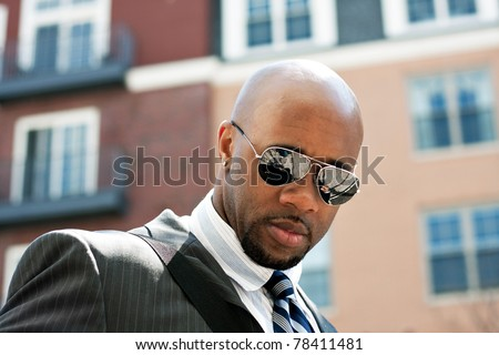 An African American business man wearing his sunglasses and business suit in the city. - stock photo