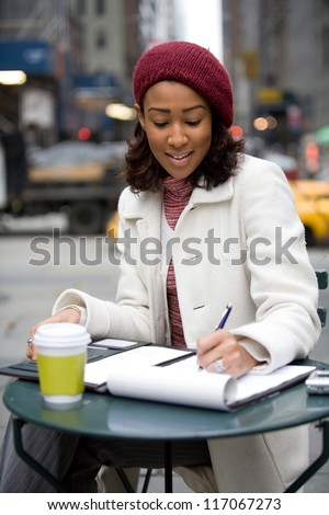 An African American business woman working in the city outdoors writes something down in her notepad. - stock photo