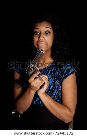 An African American has a gun and is making a funny face. - stock photo