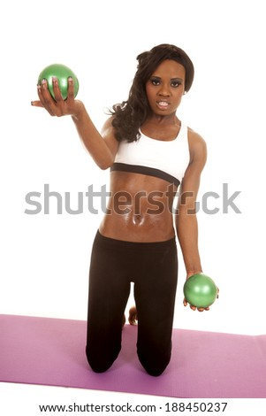 An African American kneeling down on her fitness mat, working out with green fitness balls. - stock photo
