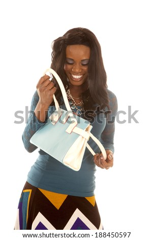an African American looking in to the bag with a smile on her face. - stock photo