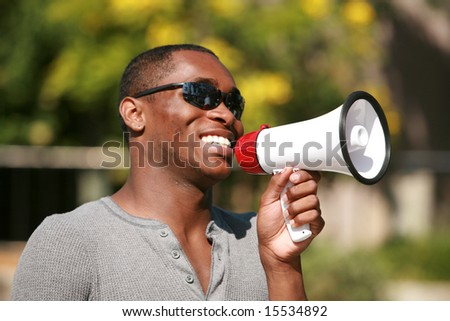 an african american male model uses a megaphone to get his message heard loud and clear - stock photo