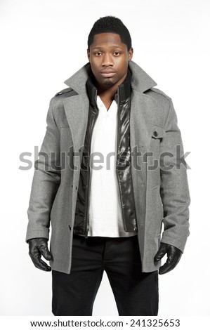 An African American male model wearing a gray jacket and white t-shirt underneath with black pants and black leather gloves in a studio setting on a white background while looking at the camera. - stock photo