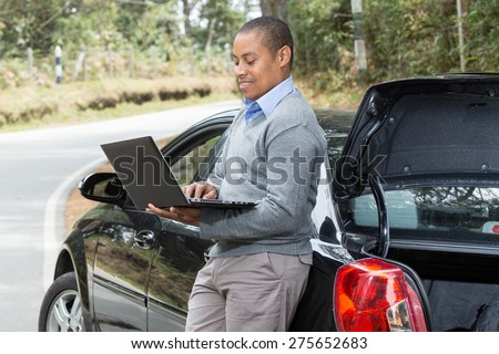 an African American man leaning against his car looking at his laptop - stock photo