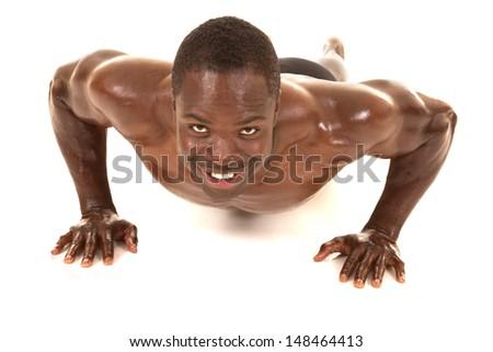 An African American man shirtless doing a pushup. - stock photo