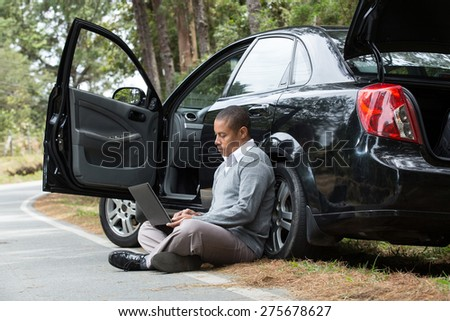 an African American man sitting beside the car on the road looking at his laptop - stock photo