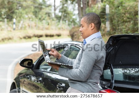 an African American man standing beside the car on the road pointing to the screen of your laptop - stock photo