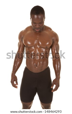 An African American man without a shirt looking down. - stock photo