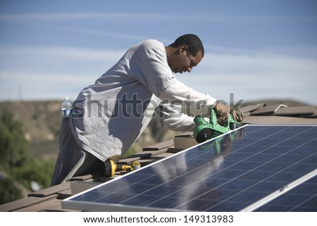 An African American man working on solar panelling on rooftop - stock photo