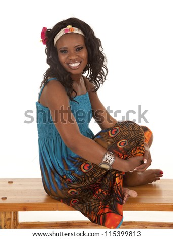 An African American relaxing on a bench in her colorful dress. - stock photo