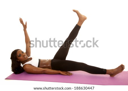 An African American stretching out her legs on her fitness mat. - stock photo