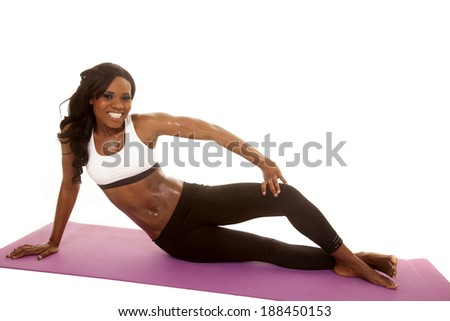 An African American woman in her fitness clothing sitting on her fitness mat. - stock photo