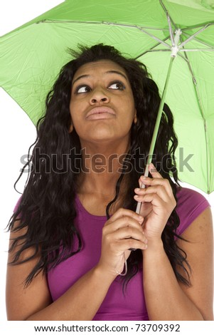 An African American woman is holding a green umbrella. - stock photo