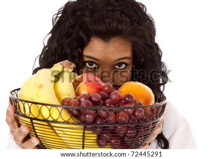 An African American woman is looking over a basket of fruit. - stock photo