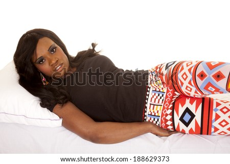 An African American woman laying on her side, in her leggings with designs. - stock photo