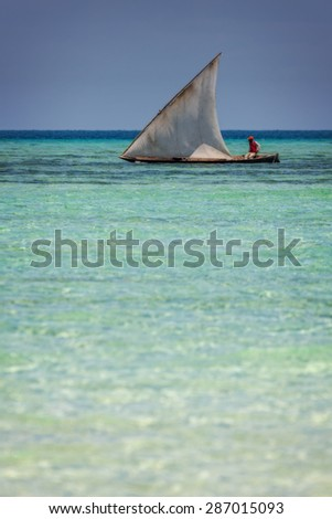 an african fisherman steering his boat over a reef on his way to his fishing grounds in clear blue weather conditions - stock photo