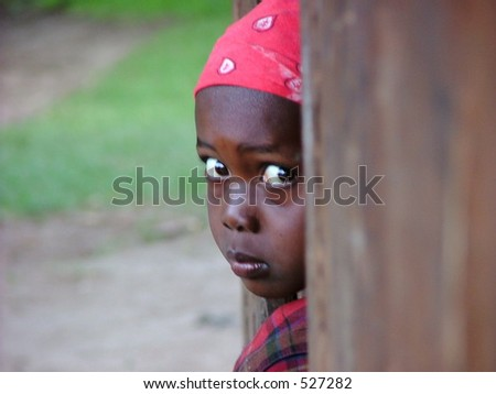 An african girl pears out of a doorway - stock photo