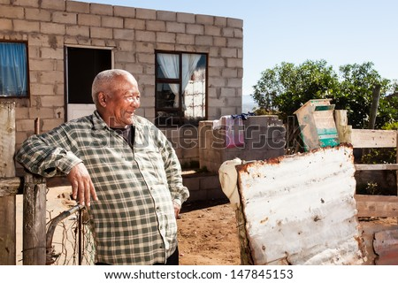 an african man leaning confidently against his fence smiling in front of his brick home in the township - stock photo