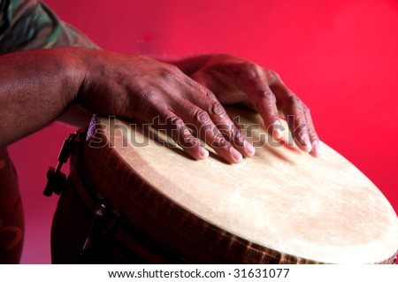 An African or Latin Djembe being played against a red background in the horizontal format. - stock photo
